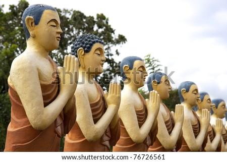 A row of Buddhist monk statues at a temple. Close to Sigiriya, Sri Lanka - stock photo