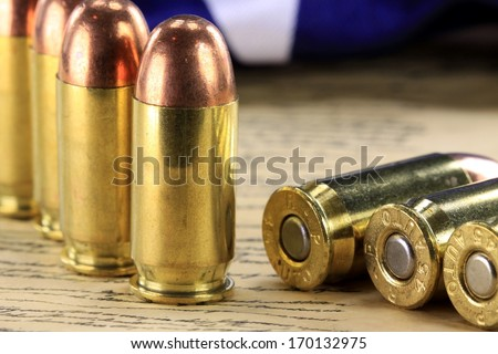 A row of 45 caliber ammunition copper plated bullets with brass slugs - stock photo