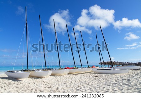 A row of catamarans on white sandy beach in Cayo Santa Maria, Cuba - stock photo