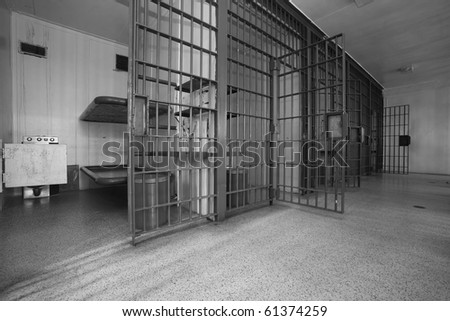 A row of 5 cells in an old jail.  The iron doors are heavy and the ammenities are few. - stock photo
