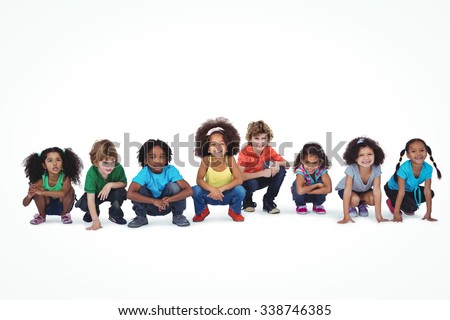 A row of children crouching down together against a white background - stock photo