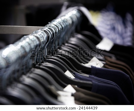 a row of clothes on hangers in the shop
