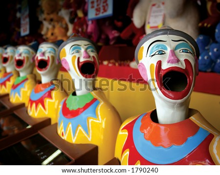 A row of clowns at an amusement park game. - stock photo