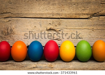 a row of colorful easter eggs in front of a wooden background - stock photo