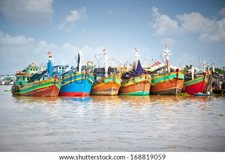 A row of colorful fishing boats berthed at the port in the Mekong Delta, Vietnam - stock photo