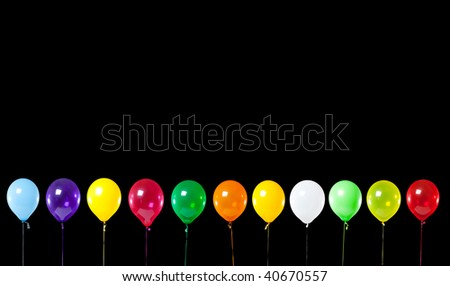 A row of colorful party balloons on black background, add copy space