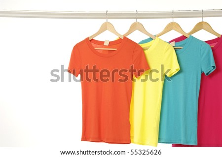 A row of colorful row t-shirts hanging on hangers on a white background