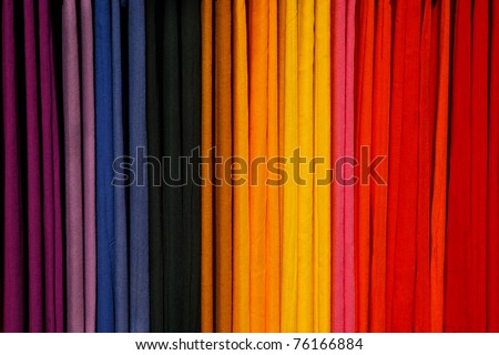 A row of colorful scarves hanging on a rack - stock photo