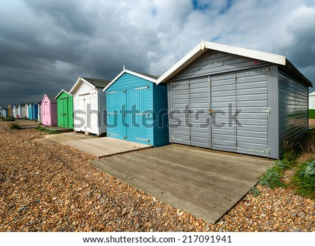 A row of colourful beach huts under a dramatic sky at St Leonards on Sea in Hastings, East Sussex - stock photo