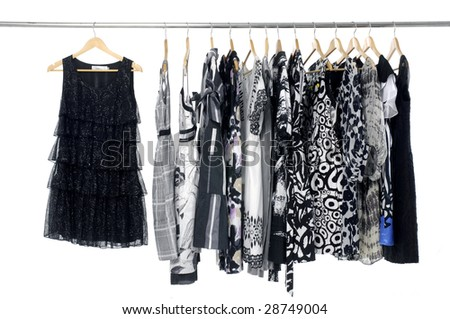 A row of designer fashion clothing hanging on hangers - stock photo