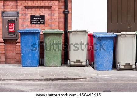 A row of different coloured wheelie bins - stock photo