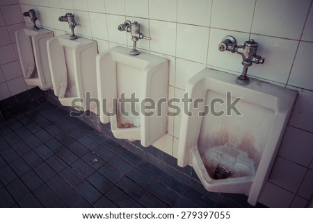 A row of dirty urinals in tiled wall in a public restroom focusing, process color - stock photo