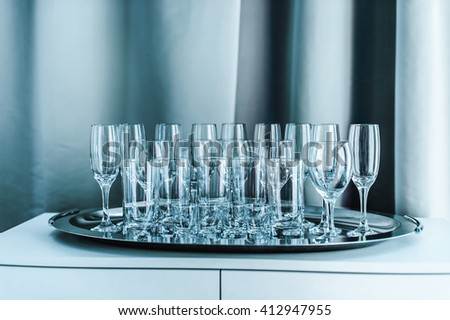a row of empty glasses on the table in blue monochrome - stock photo