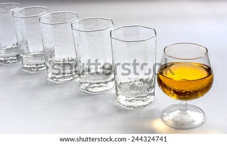 A row of empty glasses with a glass of wine at the front.  Standout and leadership concept. - stock photo