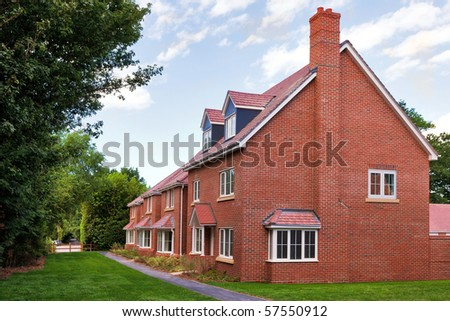 A row of empty new red brick houses on a modern UK housing estate development. - stock photo