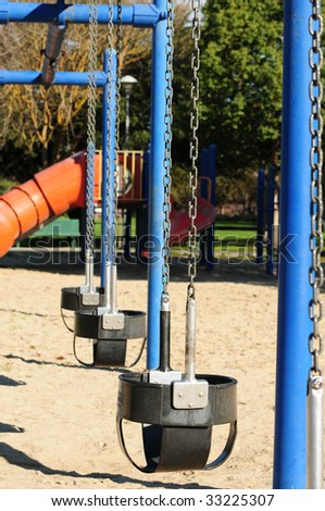 a row of empty swings on an elementary school playground - stock photo