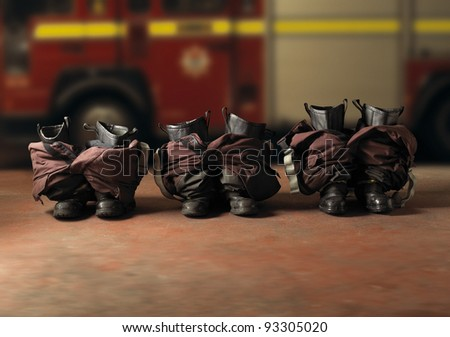 A row of fireman boots at the ready with a fire engine in the background - stock photo