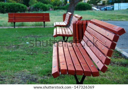 A row of freshly painted mahogany park benches