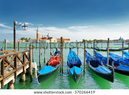 A row of gondolas parked at pier beside the Riva degli Schiavoni in Venice, Italy. Scenic view of the Venetian Lagoon. The Church of San Giorgio Maggiore on island is visible in background. - stock photo