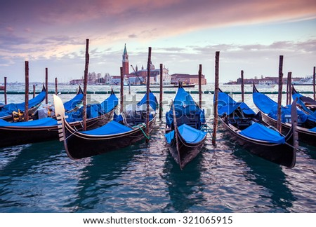 A row of gondolas parked beside the Riva degli Schiavoni in Venice, Italy. View of the Venetian Lagoon. The Church of San Giorgio Maggiore on island of the same name is visible in background - stock photo
