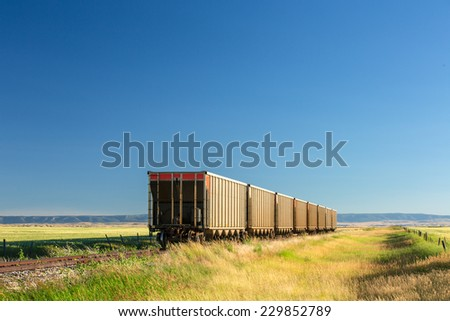 A row of grain hoppers waiting for an engine in the middle of Montana's prairie. - stock photo