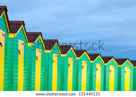 A row of green and yellow beach huts on a cloudy day.  Taken on the South Coast of England. - stock photo