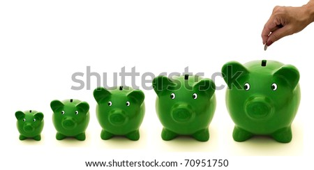 A row of green piggy bank with a white background, Investing - stock photo