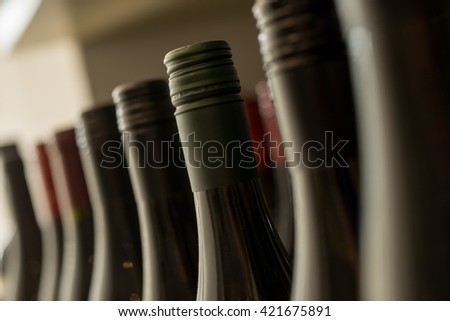 A row of heads of sealed dark bottles of wine