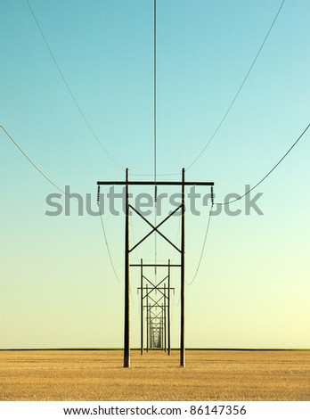 A row of high voltage electrical power lines cling to the horizon in an otherwise vast, wide open rural landscape. - stock photo