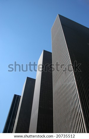 A row of Highrise buildings against blue sky - stock photo