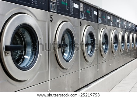 A row of industrial washing machines in a public laundromat - stock photo