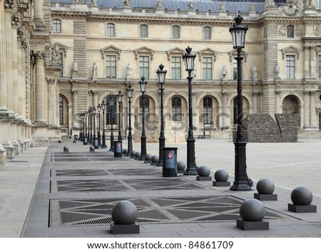 A row of lamps along a path in a courtyard in Paris, France. - stock photo