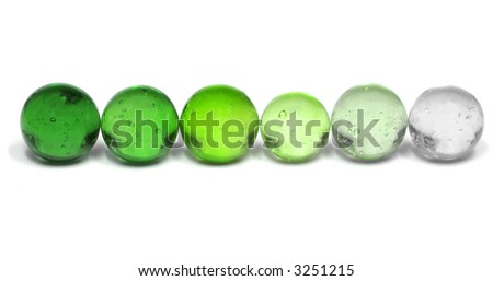 A Row of Marbles Fading from Dark Green to Nearly Clear - stock photo
