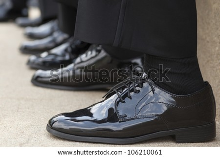 A row of men's feet in matching shoes.