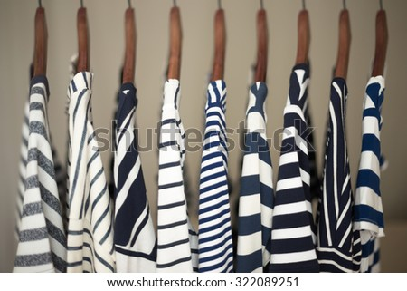 A row of navy striped tops for women on wooden hangers in a closet. - stock photo