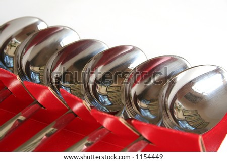 A row of neatly arranged stainless steel spoons. - stock photo
