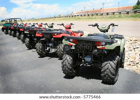 A row of new all-terrain vehicles ready to hit the trails - stock photo