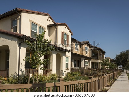 A row of new homes with fenced yards along a sidewalk. - stock photo