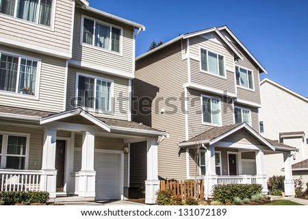A row of new townhouses from front side view - stock photo