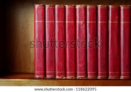 A row of old, battered, encyclopaedias on a shelf, with titles removed.  Red leather effect with gold striped trims.  Shelf has been darkened artificially to give impression of age. - stock photo