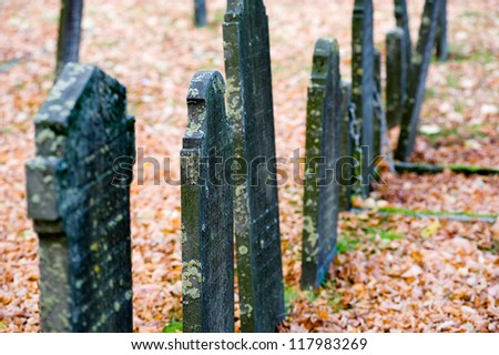 A row of old gravestones on an cemetery in the autumn - stock photo