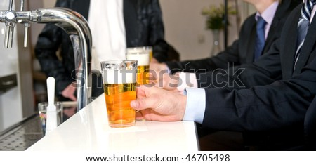 A row of people holding their beers on a bar with a shallow depth of field - stock photo