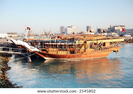 A row of Qatari dhows tied up in the Dhow Harbour, Qatar, waiting to be hired out for pleasure trips - stock photo