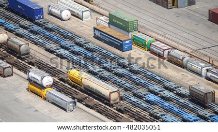 A row of railroad container cars of blue color with colorful containers around, Barcelona, Spain, July 2016
