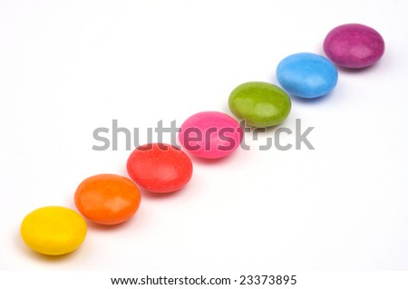 a row of rainbow coloured sweets - stock photo