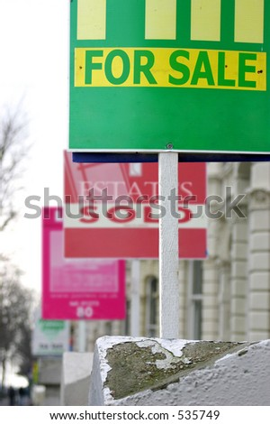 A row of real estate/estate agents' property sale and sold boards. - stock photo