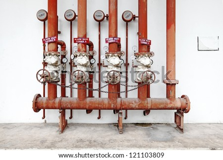 A row of red color fire fighting water supply pipeline system with valves and alarm bell hanging on a white concrete wall. - stock photo