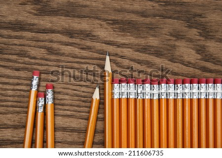 A row of red pencils on wooden surface - stock photo