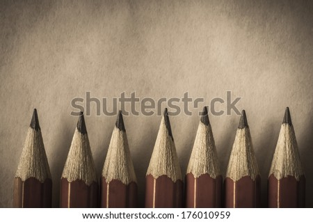 A row of red pencils with tips facing upwards against parchment textured paper which provides copy space above. Processed in a retro or vintage style. - stock photo