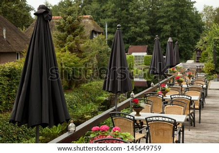 A row of rustic tables and chairs, in the balcony of an outdoor restaurant  in Giethoorn, Holland. Each table is equipped with a parasol and is decorated with flowers. - stock photo